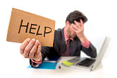 young businessman in suit and tie sitting at office desk working on computer laptop asking for help holding cardboard sign looking sad and depressed in business stress and overwork concept