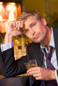 Depressed businessman in bar with drink