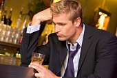 Depressed businessman with drink in bar