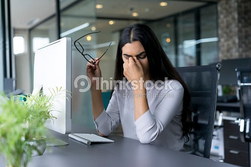 Depressed businesswoman rubbing eyes in office : Stock Photo