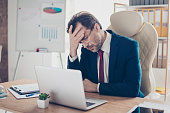 Depressed entrepreneur realtor is holding his head with hand, he is tired and frustrated, sitting in the office at his work place