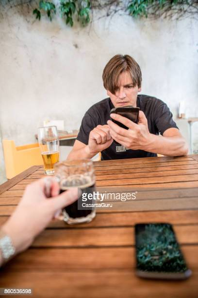 Depressed Entrepreneur Texting While Having A Drink At The End Of The Working Day
