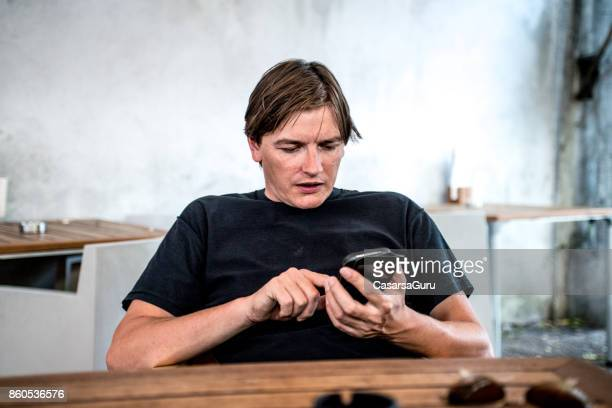 Depressed Entrepreneur Texting While Waiting For A Drink At The Pub