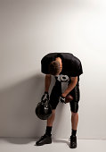 Depressed football player standing in front of a white background