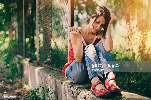 Depressed girl at the school yard smoking cigarette