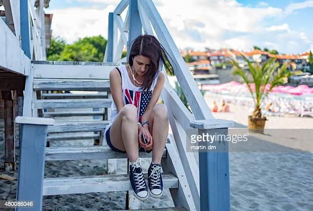 Depressed girl at wooden stairs on the beach