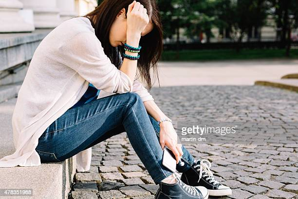 Depressed girl sitting at the street