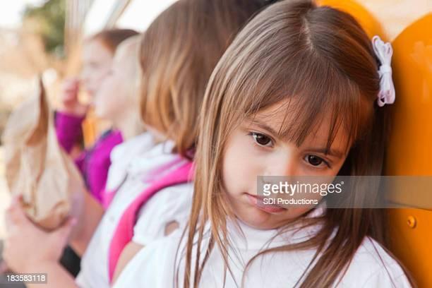 Ein deprimierter kleines Mädchen gelehnt auf Schulbus mit anderen Studenten