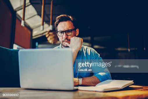 Depressed male entrepreneur feeling headache can't solve problems with finance checking report on netbook.Stressed manager worried about documentation on laptop failure with saving on software : Stock Photo