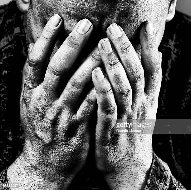 Depressed man, hands covering face