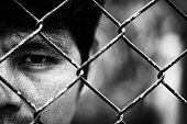 Depressed man standing behind a fence ,close up on face in white tone, abuse concept