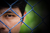 Depressed man standing behind a fence ,close up on face , abuse concept
