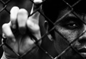 Depressed man standing behind a fence, hand grabs steel mesh cage,close up on face in white tone, abuse concept