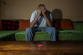 Suicidal man, Depressed man suffering from suicidal depression want to commit suicide by taking strong medicament drugs and pills pain killers while he sitting in his dark room selective focus moody d
