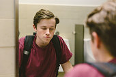 Depressed teen student helplessly stares at his reflection in bathroom mirror.