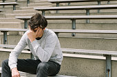 Depressed teen sitting alone on bleachers.