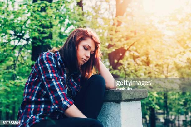 Depressed teenage girl in the park