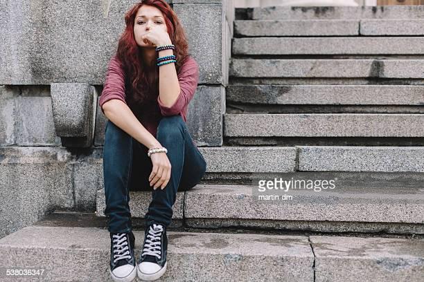 Depressed teenage girl sitting on stairs