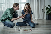 Shocked man is looking at different pills while woman is sitting and crying on floor.