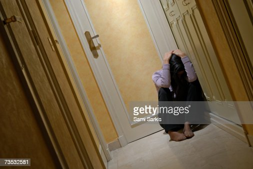 Depressed woman sitting in corridor with head in hands : Stock Photo