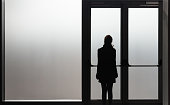 Depressed woman waiting in front a glass door in a white room ready to react - Disease - Abuse - phobia Concept.
