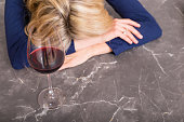 Depressed woman with wine glass resting her head on kitchen counter