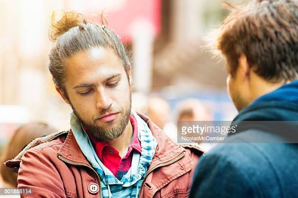 Depressed young man sadly looks down during conversation
