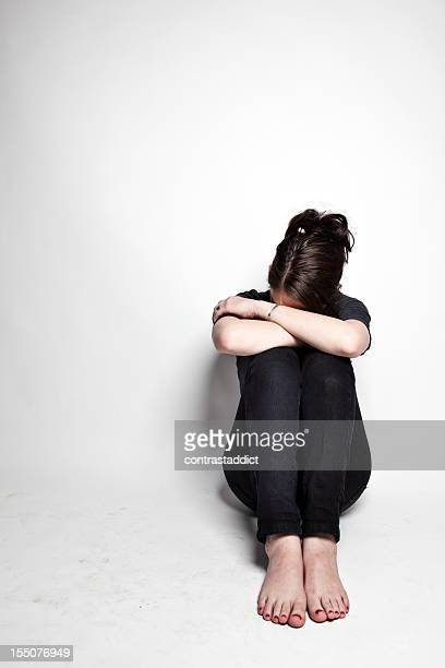 Depressed young woman in black sits, hiding face