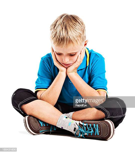 Depressed-looking little boy sits looking down head in hands