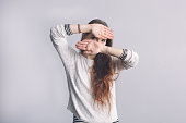 Girl with long hair covers his face with his hands.