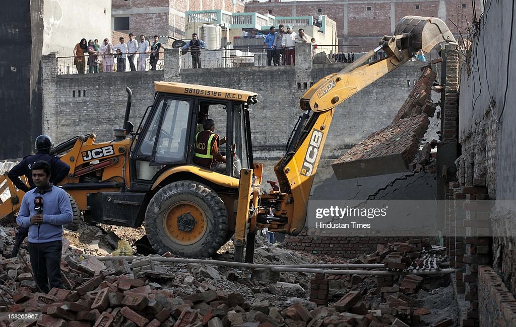 MCD dept demolition a side wall, after a wall collapsed caused death of 5 children and serious injury to one child at Dallupura village near New Ashok Nagar on December 12, 2012 in New Delhi, India.