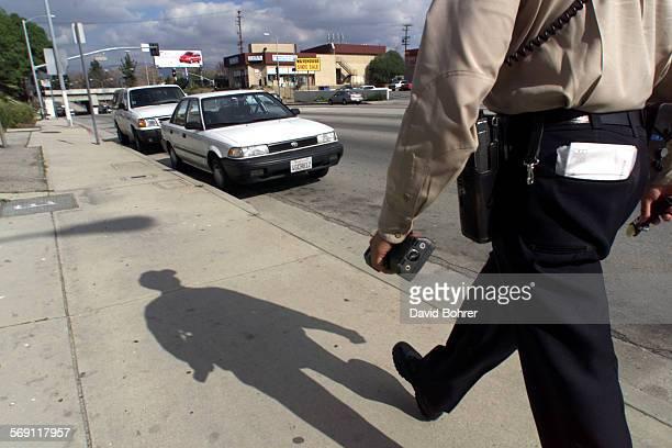 Dept of Transportation Traffic Officer Manny Garcia walks along Sepulveda Blvd to write parking citations for violators in a two hour parking zone in...