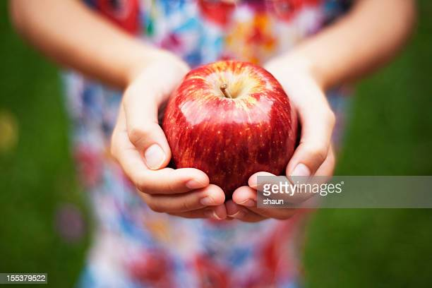 Depth of field apple held by a girl in colored dress outside