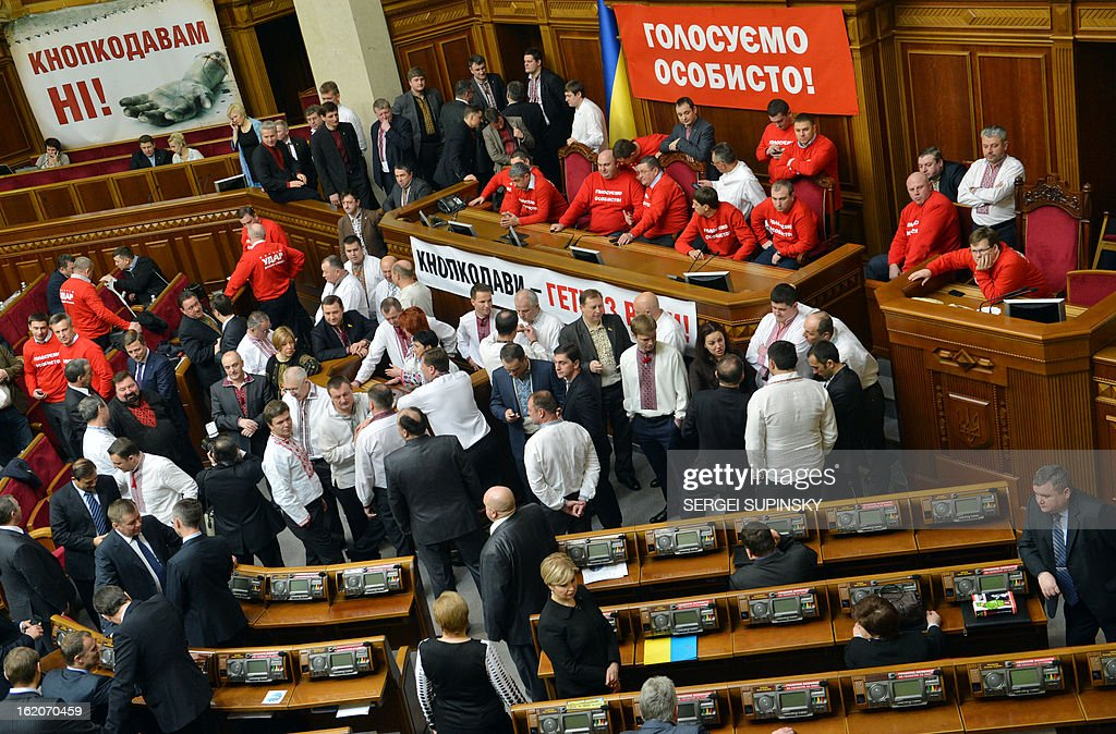 Deputies of opposition block the Ukrainian parliamentary tribune next to posters reading 'Vote personally', in Kiev on February 19, 2013, to prevent the opening of the session. The dispute in Ukraine's one-chamber parliament, known as the Verkhovna Rada, centres on opposition demands for each deputy to vote individually. Voting in the Ukrainian legislature is done electronically and lawmakers can delegate the right to vote to their colleagues.