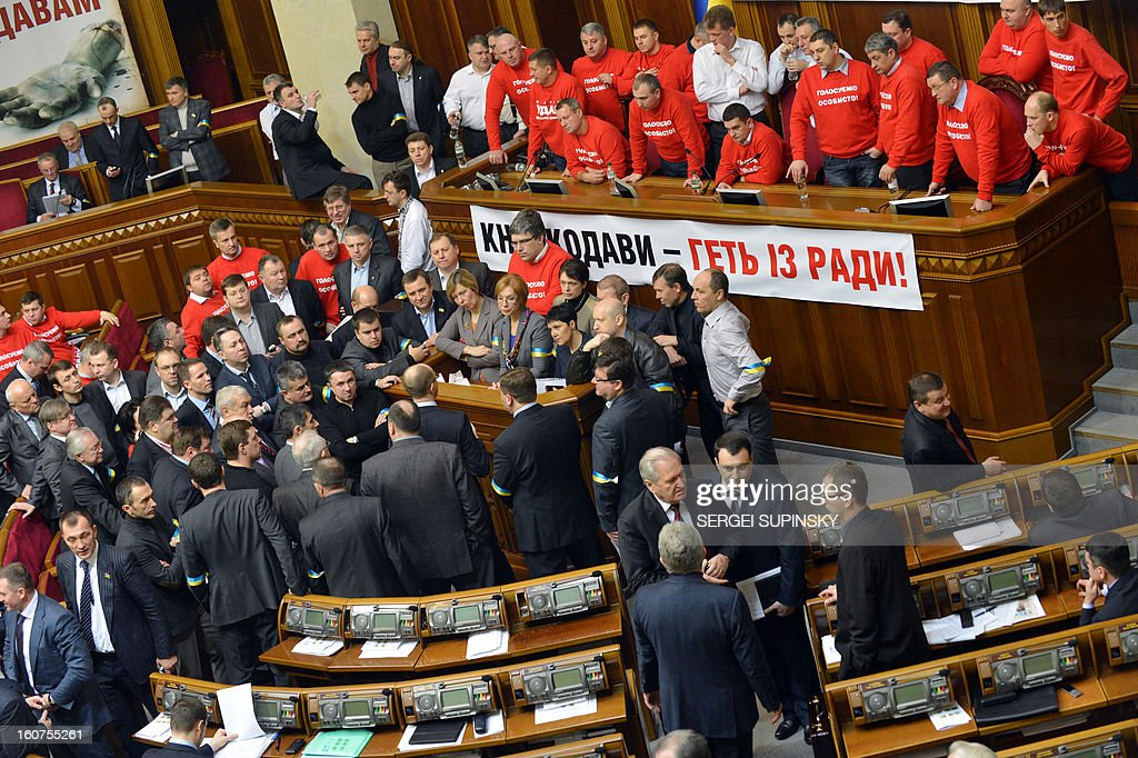 Deputies of Ukrainian opposition block the parliament's platform during their openning session in Kiev on February 5, 2013. The opposition deputies were trying to reclaim respect for the individual's right to vote, after having accused pro-government deputies of giving away their votes in their absence. AFP PHOTO/ SERGEI SUPINSKY