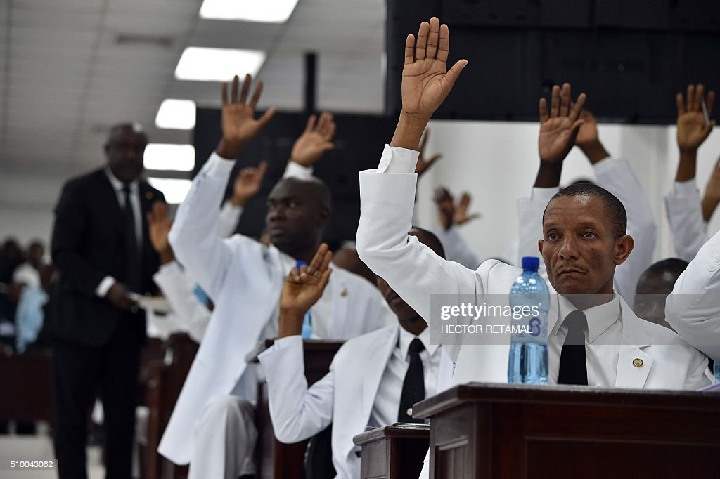Deputies raise their hands during a debate prior the election of a provisional president at the National Assambly in the Haitian Parliament, in Port-au-Prince, on February 13, 2016. Haitian lawmakers were set to elect an interim president to fill the power vacuum following the departure of Michel Martelly, after a vote to choose his replacement was postponed over fears of violence. / AFP / HECTOR RETAMAL
