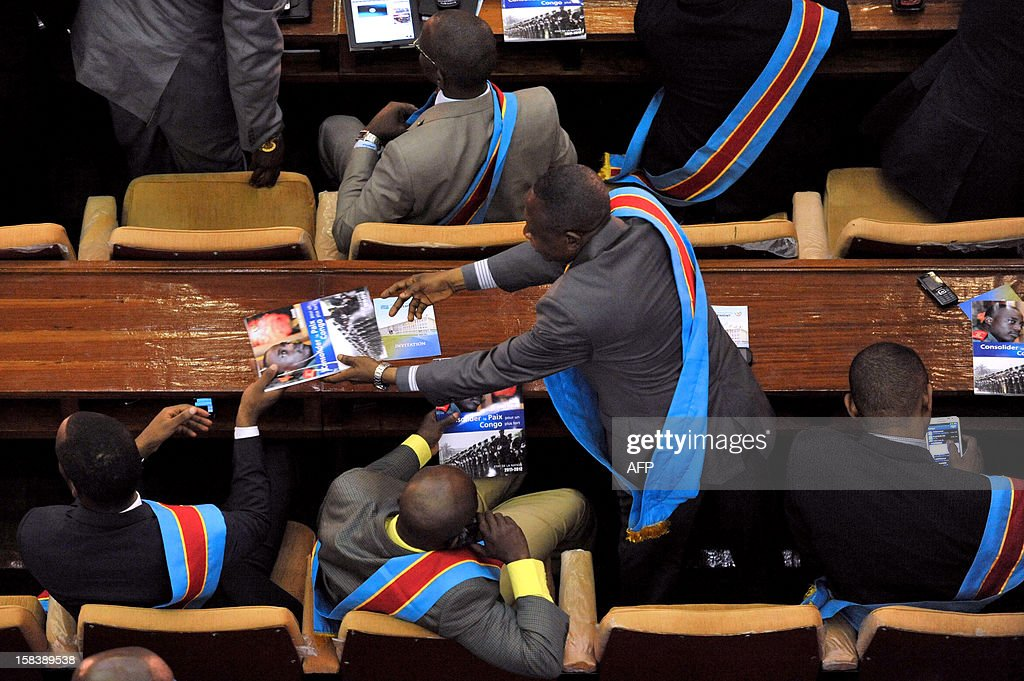 Deputies read a magazine bearing a portrait of the Democratic Republic of Congo President with the headline 'Consolidate Peace for a stronger Congo' on December 15, 2012 at the Parliament in Kinshasa's People Palace. Kabila on December 15 vowed that defence would be a top priority for his government after the recent brief rebel takeover of a key city in the country's volatile east. AFP PHOTO / JUNIOR D.KANNAH