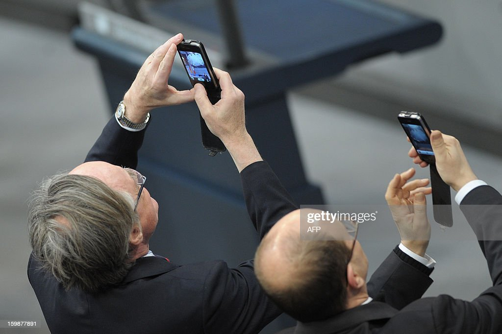 Deputies take a picture with their smartphone before a joint session of the French National Assembly and the Bundestag at the German lower house of Parliament Bundestag on January 22, 2013 in Berlin as part of the celebrations marking the 50 years of the Elysee Treaty, launched after WWII as a French-German cooperation. In signing the landmark treaty on January 22, 1963, then French president Charles de Gaulle and West German chancellor Konrad Adenauer sealed a new era of reconciliation between the former foes which has since driven European unity.