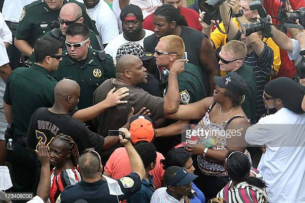 Deputies try to maintain calm after a shouting match erupts into pushing as people wait for a verdict in the George Zimmerman trial outside the...