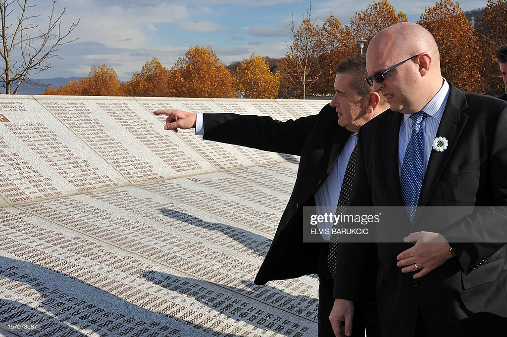 Deputy Assistant of US Secretary of State for European and Eurasian Affairs Philip Reeker (R) walks by the Memorial Wall as he pays his respects to Bosnian Muslim victims of the 1995 Srebrenica massacre at Memorial Cemetery in Potocari, near Srebrenica, on November 28, 2012, accompagnied by Memorial Cemetery 's manager Mersed Smajlovic (L). Reeker arrived for an official three day visit to Bosnia amid a post-electoral feud in which Serbs are contesting a Muslim victory in the local October elections in the politically troubled Eastern-Bosnian city of Srebrenica.