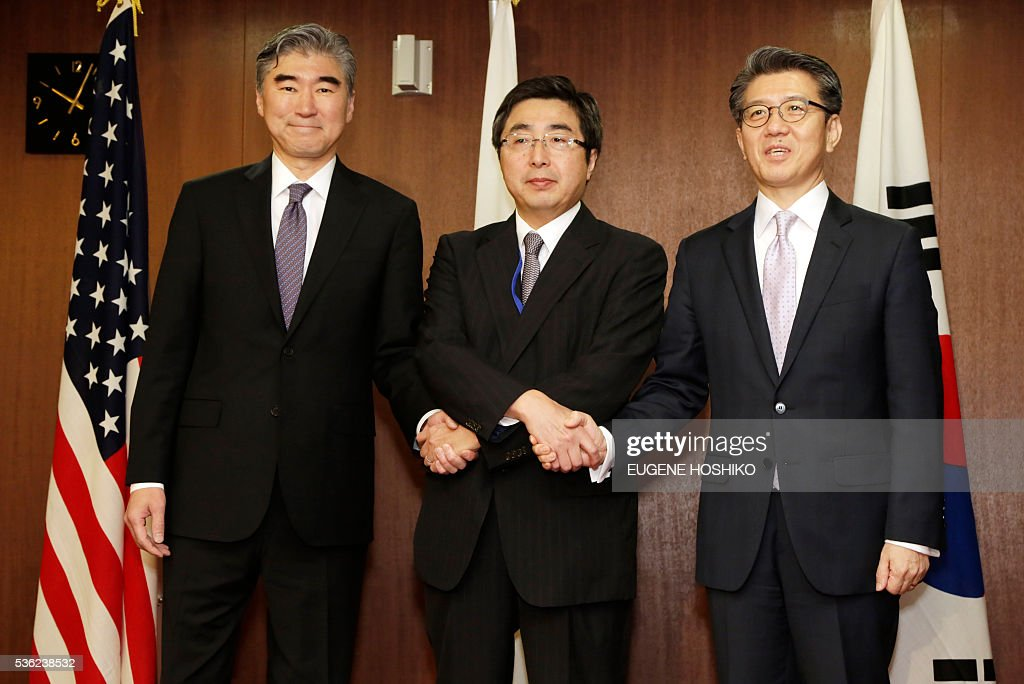 US deputy assistant secretary of state for Japan and Korea Sung Kim (L), director general of the Foreign Ministrys Asian and Oceanian Affairs Bureau Kimihiro Ishikane (C) and Special Representative for Korean Peninsula Peace and Security Affairs Kim Hong-kyun shake hands prior to their meeting at the Japanese Foreign Ministry on June 1, 2016. / AFP / POOL / Eugene Hoshiko