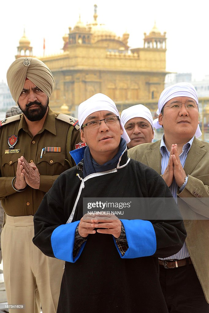 Deputy Chairperson of Bhutan National Council, Sonam Kinga (C) and Bhutan Member of Parliament, Tashi Wangyal (R) pay their respects at the Sikh Shrine Golden temple in Amritsar on December 2, 2012.