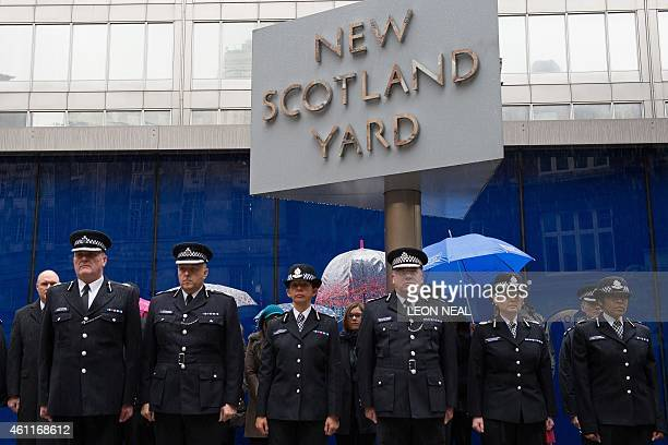 Deputy Commissioner of Britain's Metropolitan Police Craig Mackey leads police officers in a two minute silence outside Scotland Yard in London on...