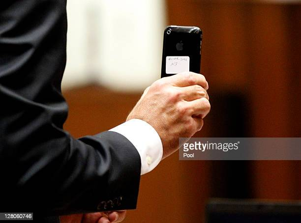 Deputy district attorney David Walgren holds Dr Conrad Murray's iPhone which was enterd as evidence during Murray's involuntary manslaughter trial at...