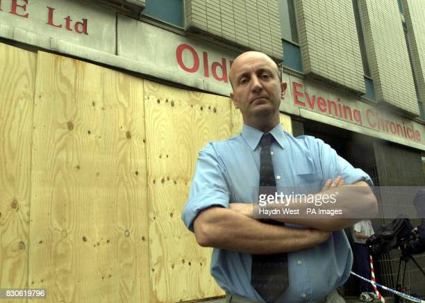 Deputy editor of Oldham Evening Chronicle Dave Whaley stands outside the newspaper's boardedup offices which were attacked in the early hours during...