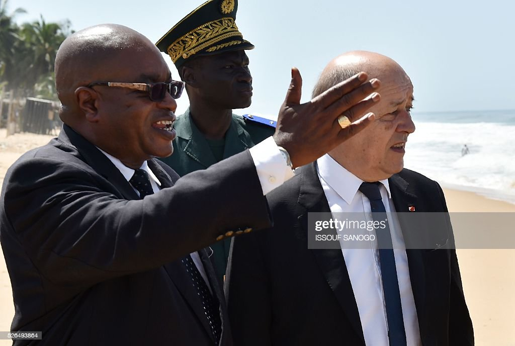 Deputy Mayor of Grand-Bassam Guy Daniel Ouegnin (L) gestures next to French Defence Minister Jean-Yves Le Drian on the beach of the Hotel l'Etoile du Sud in Grand Bassam on April 30, 2016, which was hit by a jihadist attack in March that left 19 people dead. France will increase the number of its troops in Ivory Coast, Defence Minister Jean-Yves Le Drian said on a trip to the African nation which hosts a regional base for French forces. / AFP / ISSOUF