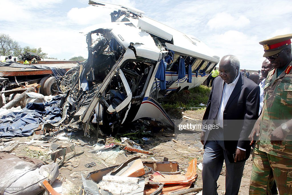 Deputy minister for Works and Supply Colonel Panji Kaunda with a Provincial Army representative inspects the accident scene after a Zambia postal service bus carrying 74 passengers collided head-on with a heavy goods truck on February 7, 2013 in Chibombo, police say. Sources say the death toll is believed to have risen to 59. Zambia Army and police officers helped in the rescue efforts at the accident scene 45 kilometres north of Lusaka.