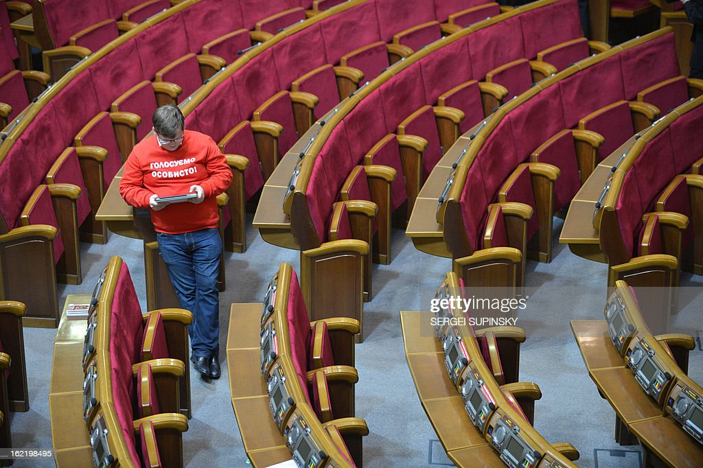 """A deputy of the Ukrainian opposition party UDAR ( Punch) wears a T-shirt, reading 'Vote personally,"""" as other deputies of the party block the parliamentary tribune to prevent the opening of the session in Kiev on February 20, 2013. The dispute in Ukraine's one-chamber parliament, known as the Verkhovna Rada, centers on opposition demands for each deputy to vote individually. Voting in the Ukrainian legislature is done electronically and lawmakers can delegate the right to vote to their colleagues."""