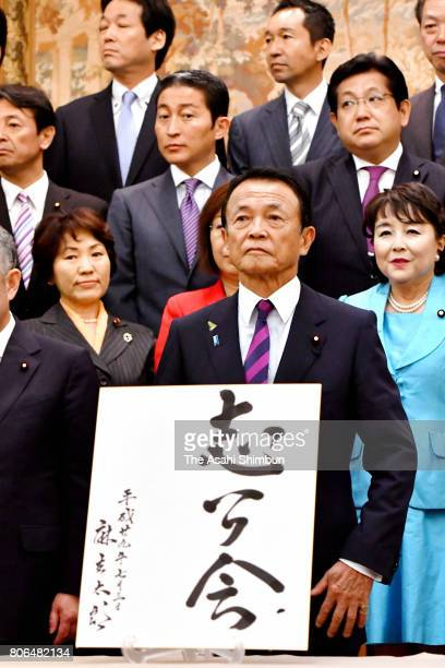 Deputy Prime Minister and Finance Minister Taro Aso poses for photographs with his fellow lawmakers during the foundation meeting of the ruling...