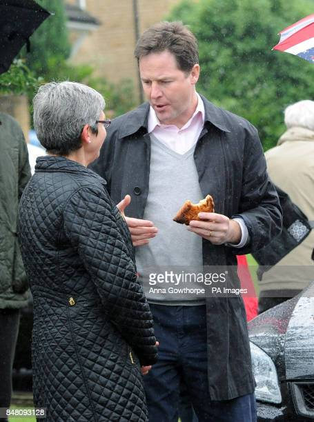 Deputy Prime Minister Nick Clegg eats a pasty as he chats to a guest at a street party in Sheffield during the Diamond Jubilee celebrations